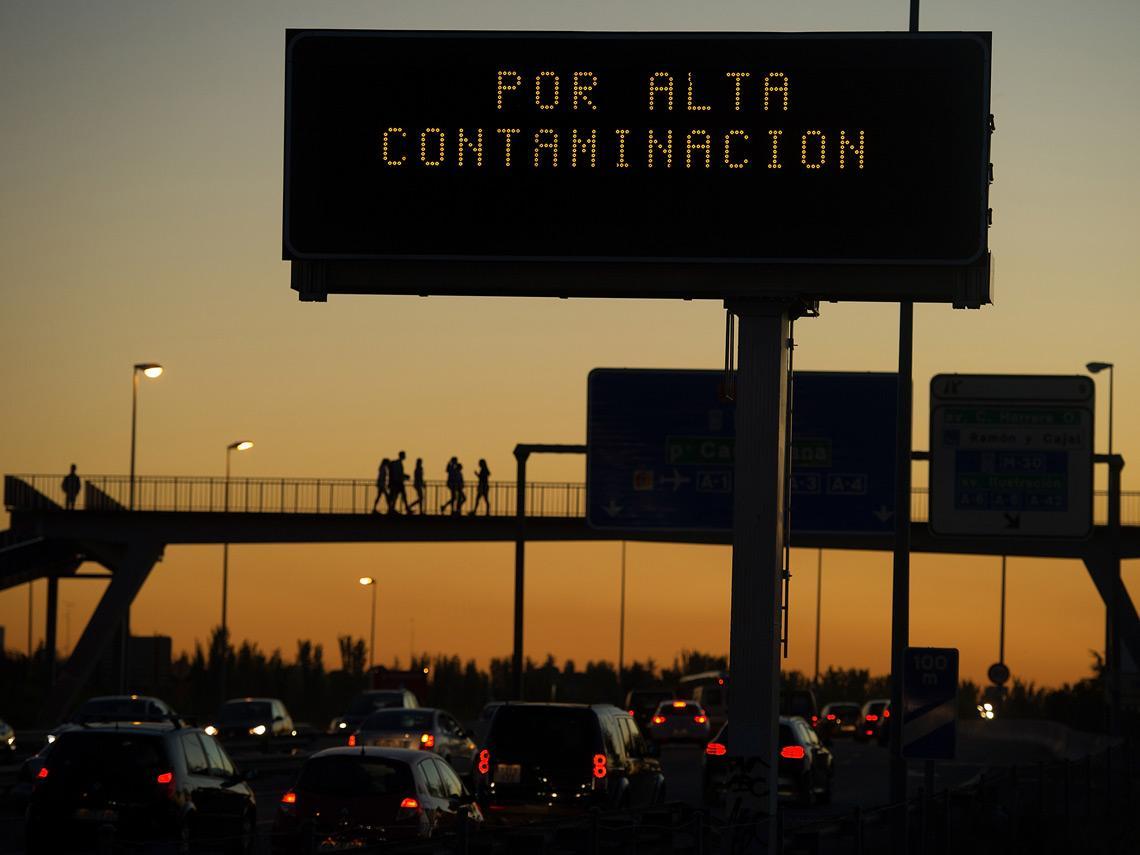 Autovía con coches y cartel de alta contaminación