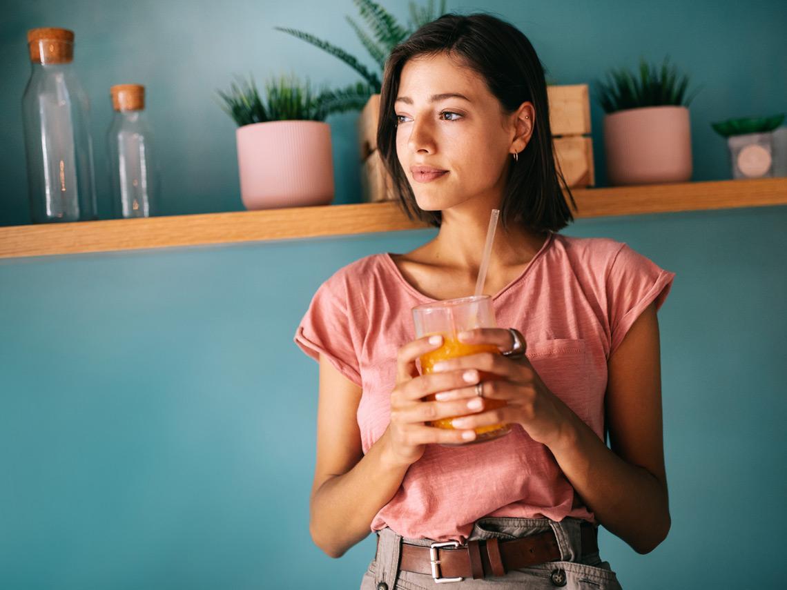 Mujer sosteniendo un zumo de naranja